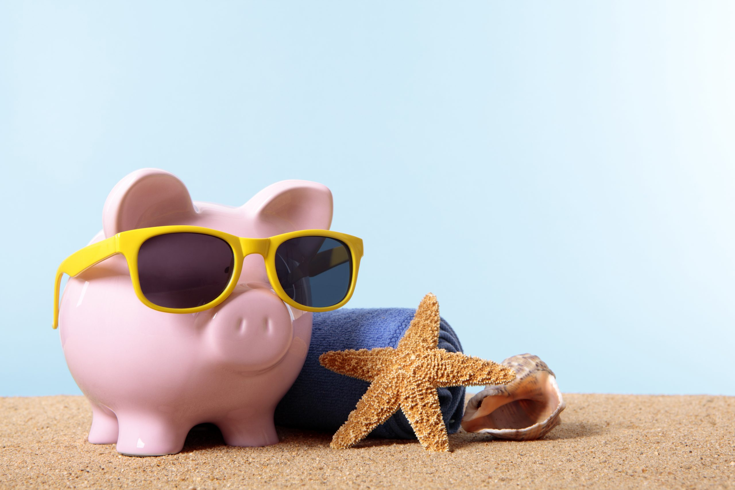Pink piggy bank on a beach with sunglasses and beach towel.  Space for copy.